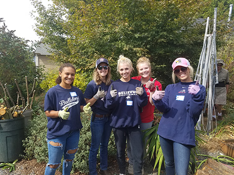 image of  Bellevue sofyball players doing some yard work